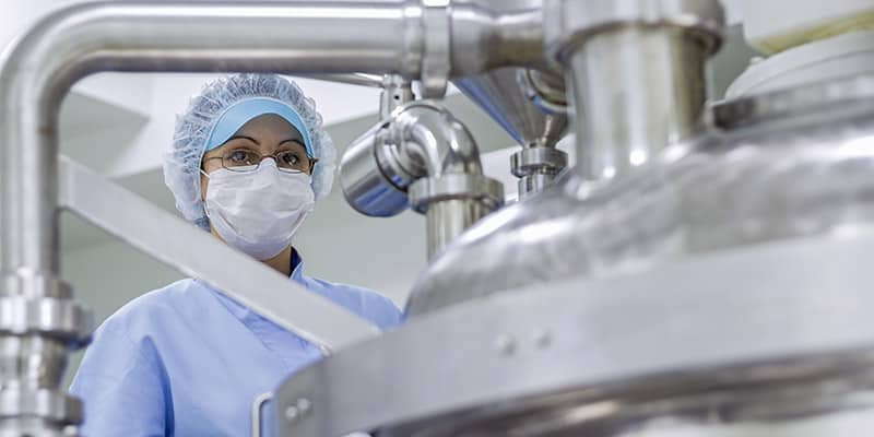 Female Worker Wearing Protective Clothing in Pharmaceutical Plant